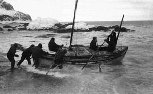 Shackleton and crew launch the lifeboat, James Caird, at the start of their journey to South Georgia.  Photo taken by expedition photographer, Frank Hurley, April 1916.